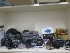 A collection of four SLR cameras with assorted lenses: Minolta X-700, Nikon F55, Canon T70,