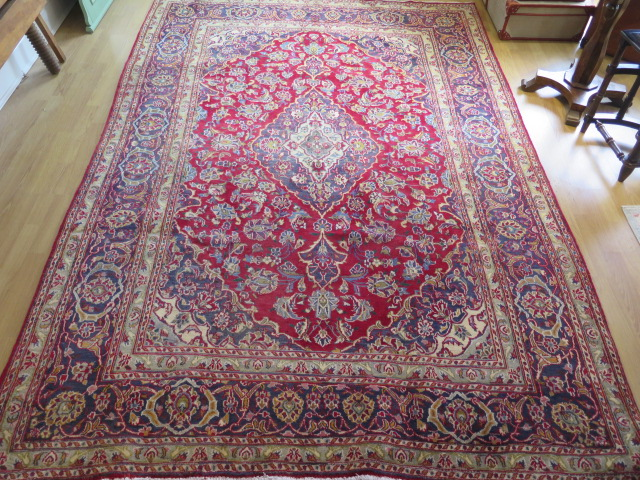 A rich red ground hand woven woollen full pile Persian Kashan carpet with traditional floral