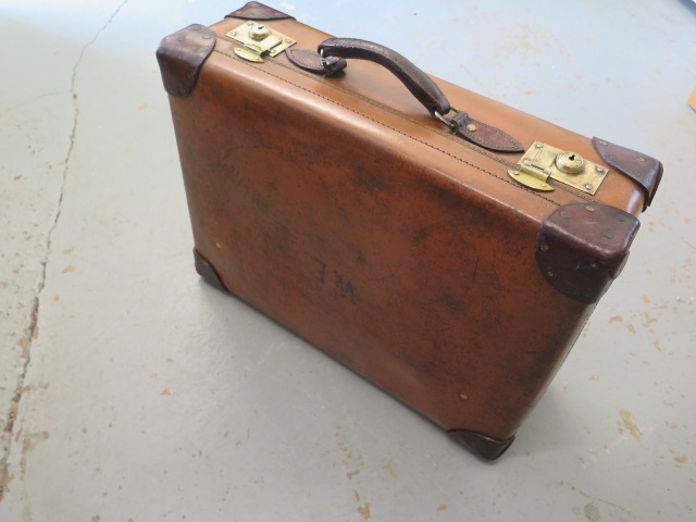A Vintage fibre and leather suitcase with brass locks in good polished usable condition, 19cm x 56cm