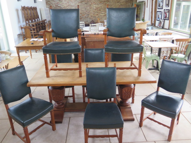 An oak refectory table on carved bulbous supports with 8 green leather upholstered chairs, 76cm tall