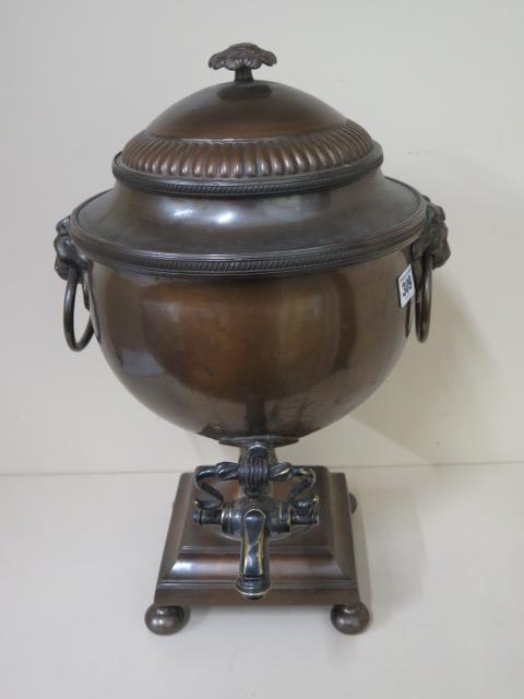 A bronzed samovar with lions head handles, 44cm tall, generally good with iron heat weight,