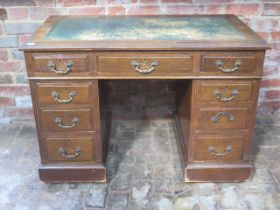 A late Victorian / Edwardian oak 9 drawer twin pedestal desk with a leather insert top, 75cm tall