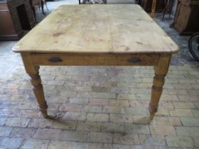 A Victorian stripped pine table with two end drawers and a side drawer on turned legs, 77cm tall x