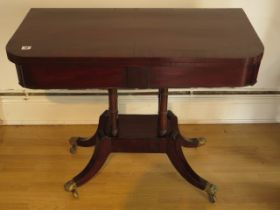 A 19th century mahogany foldover card table on four pillar support and splayed legs on brass hairy