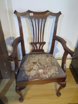 A Georgian American walnut open armchair with a vase shaped splat and scroll arms on cabriole shaped
