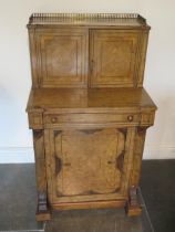 A good Victorian walnut writing desk with a two door brass galleried top with fitted interior