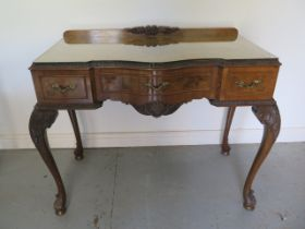 A walnut three drawer serpentine fronted table on acanthus carved cabriole legs, 90cm tall x 114cm x