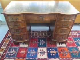 A mahogany serpentine fronted nine drawer kneehole desk with a leather inset top, 75cm tall x