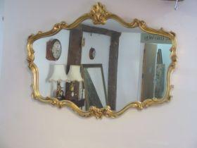 An ornate gilt framed modern mirror, 81cm x 107cm, in good condition