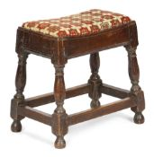 A QUEEN ANNE OAK JOINT STOOL C.1705 with a later needlework drop-in seat, on ring turned baluster