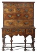 A QUEEN ANNE WALNUT CHEST ON STAND C.1710 with two short and three long feather banded drawers,