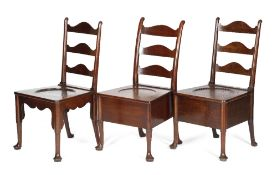 THREE GEORGE II MAHOGANY COMMODE CHAIRS C.1740-50 each with a shaped ladder back, above a dished