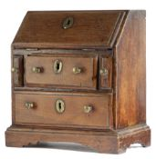 AN OAK MINIATURE BUREAU 18TH CENTURY with a hinged fall revealing three pigeonholes, above two