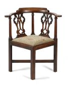 AN EARLY GEORGE III MAHOGANY CORNER CHAIR C.1760-70 the curved top rail above a twin pierced splat