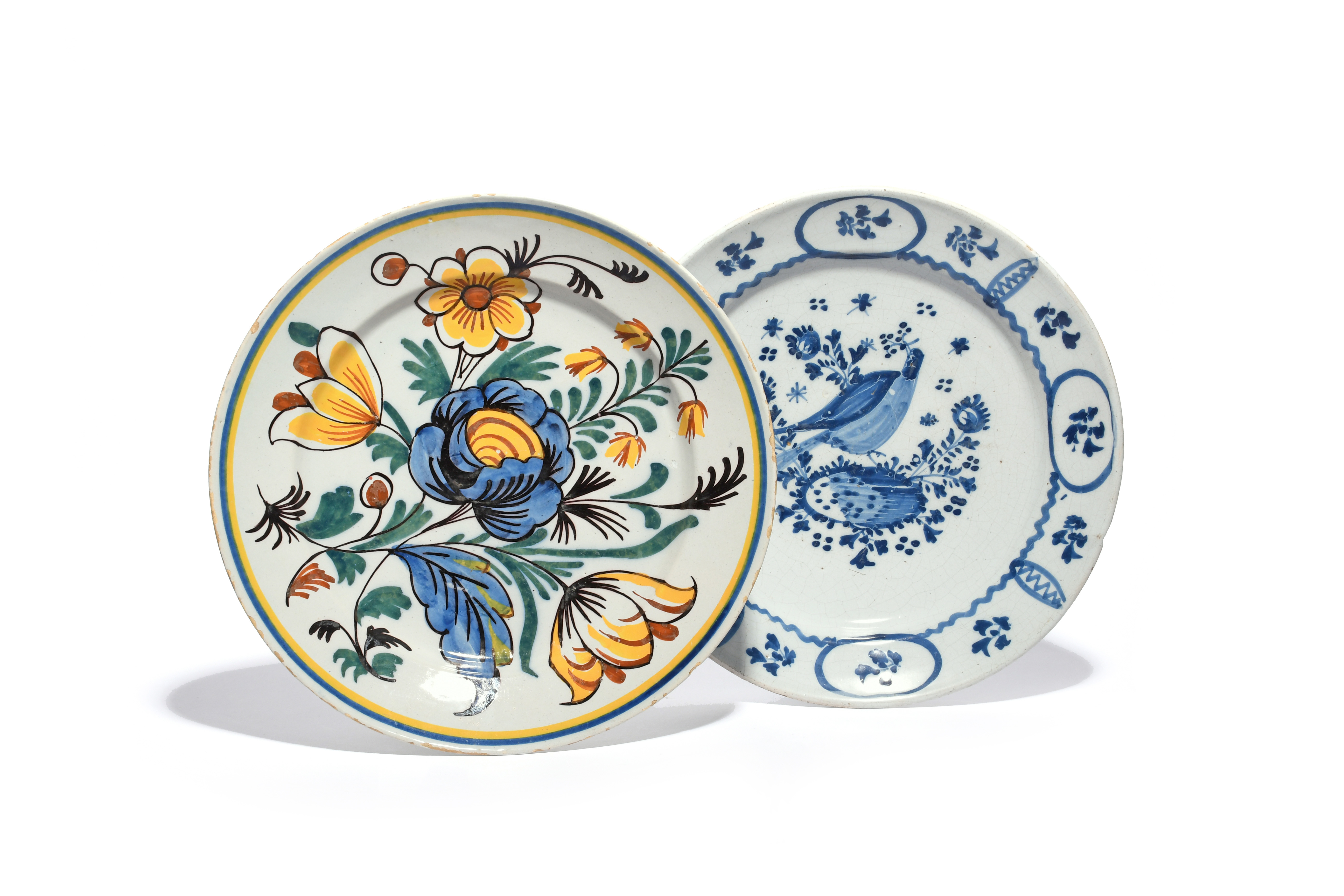 Two Delft chargers 18th century, one boldly decorated with tulips and other flowers in polychrome