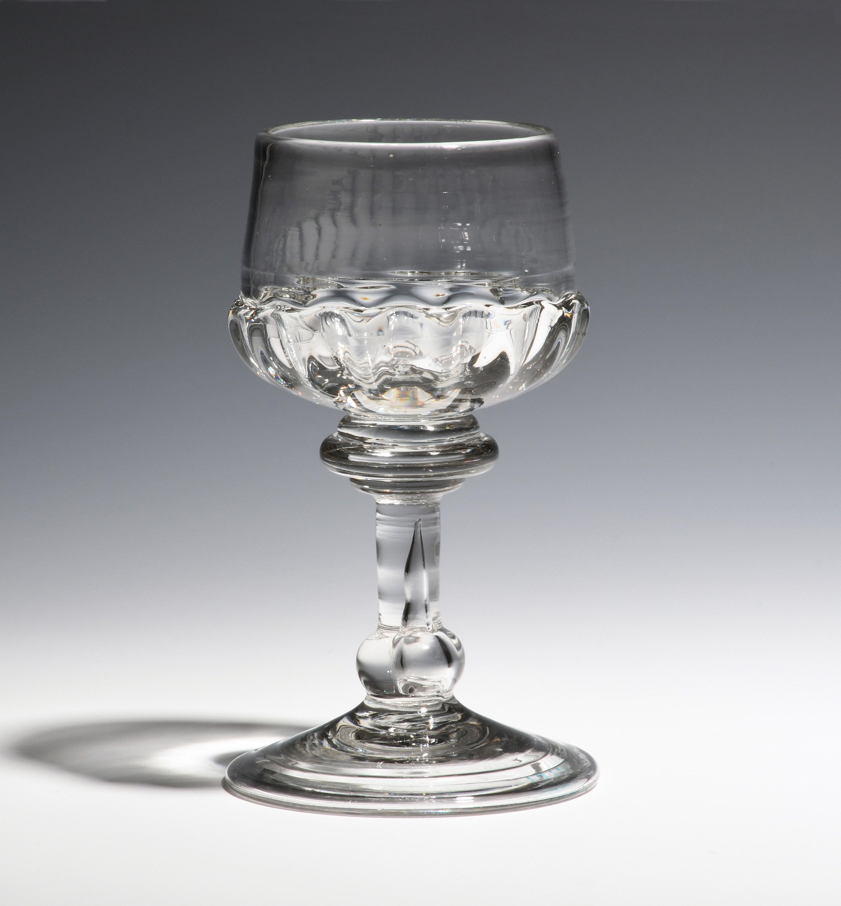 A mead glass c.1730, the cup bowl with gadroon moulding, raised on a stem with annulated top,