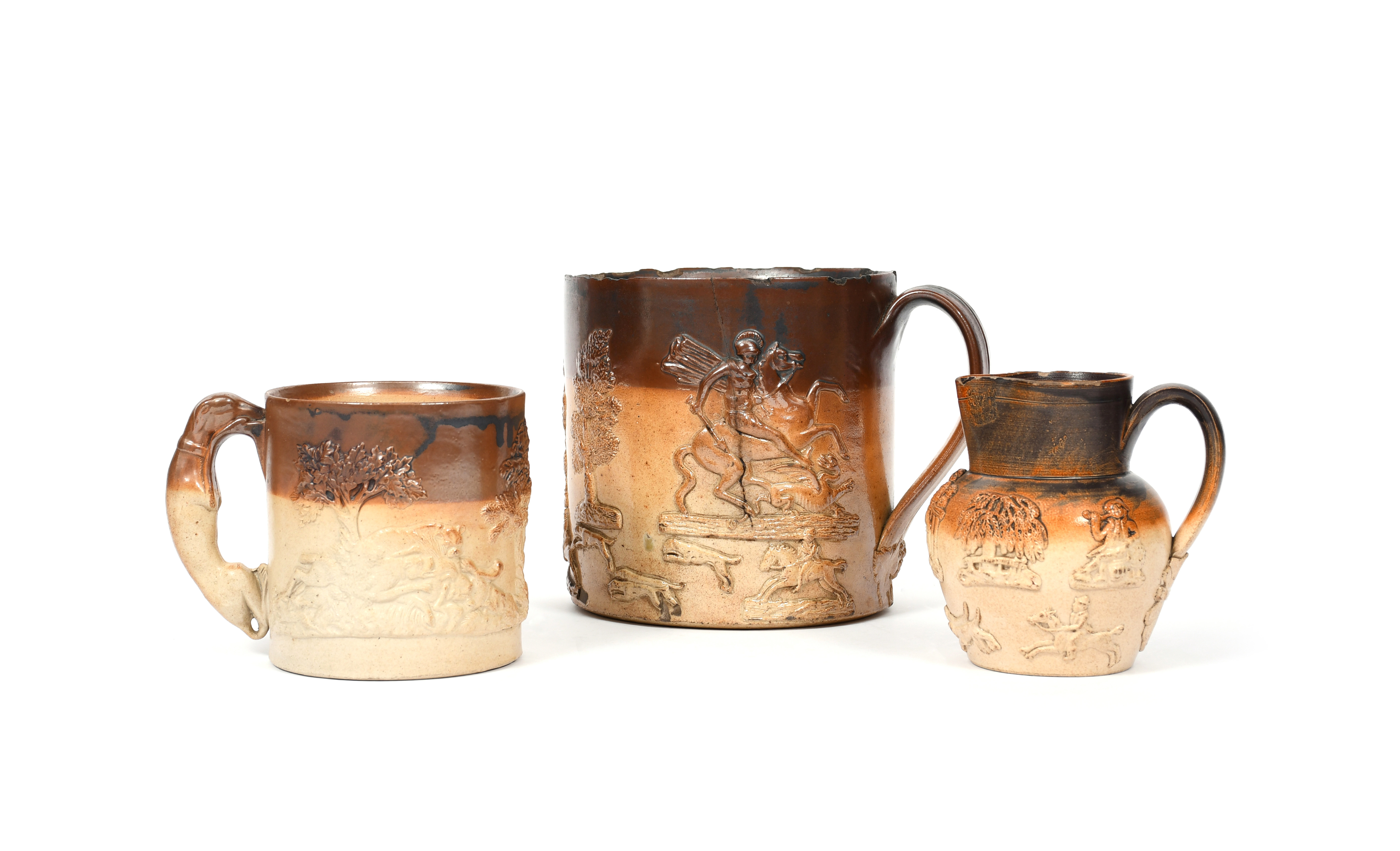 Two brown stoneware mugs and a jug 19th century, the largest mug of generous form and sprigged