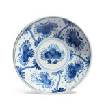 An early London delftware charger c.1660, painted in blue with a stylized flower to the well