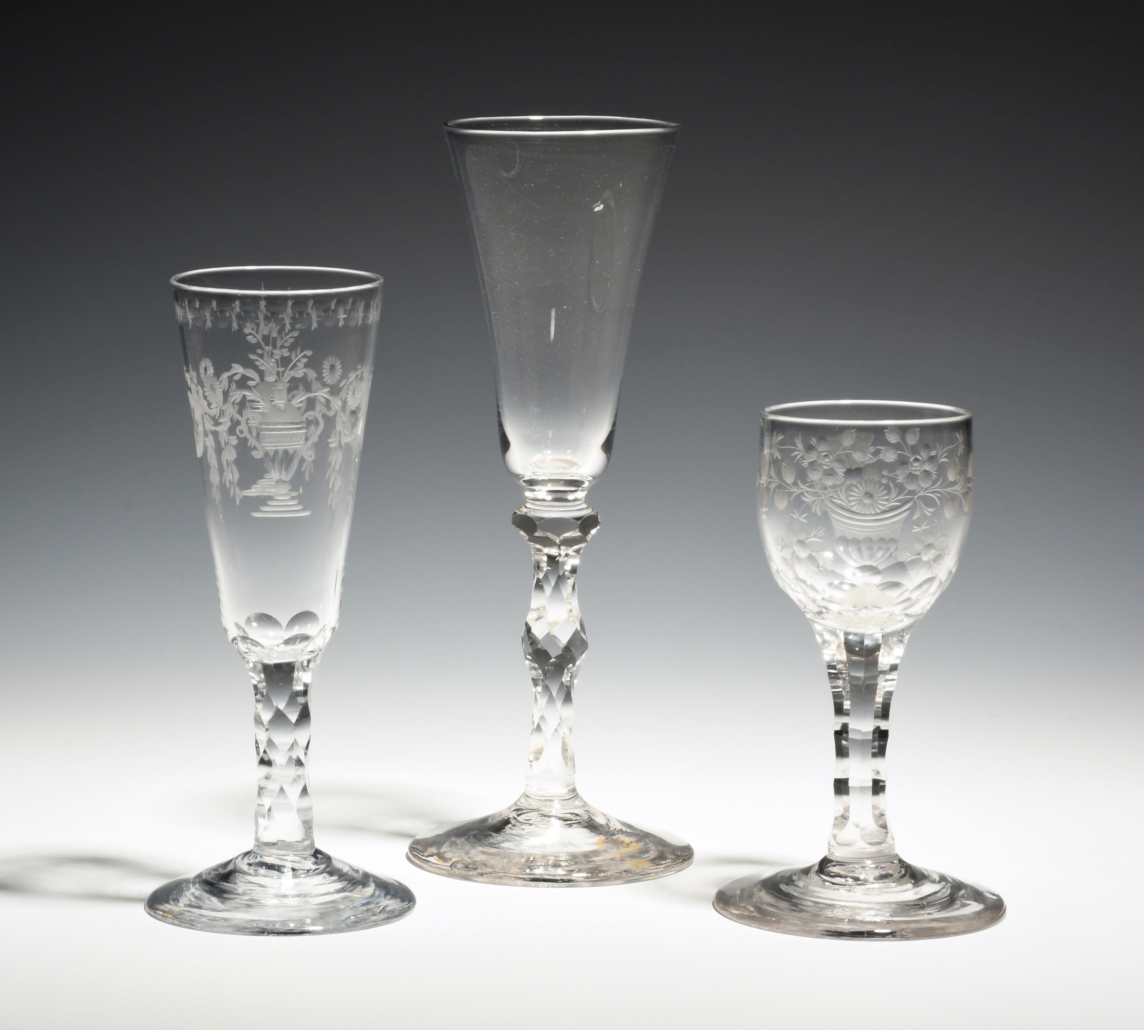 Three glasses c.1770-80, two ale glasses on faceted stems, the last a wine glass with ovoid bowl
