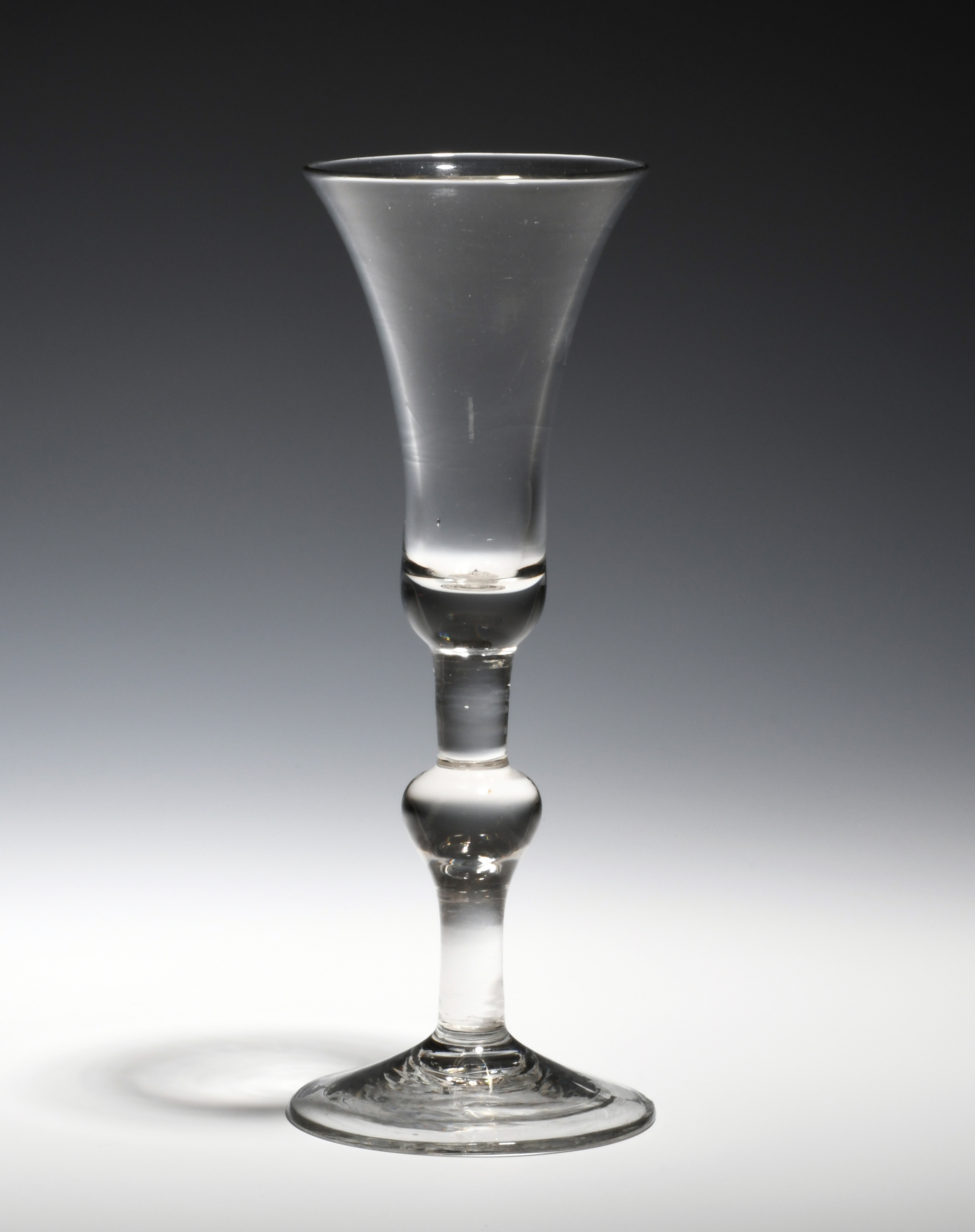 An ale glass c.1730, the bell bowl raised on a plain stem with baluster knop above a conical foot,