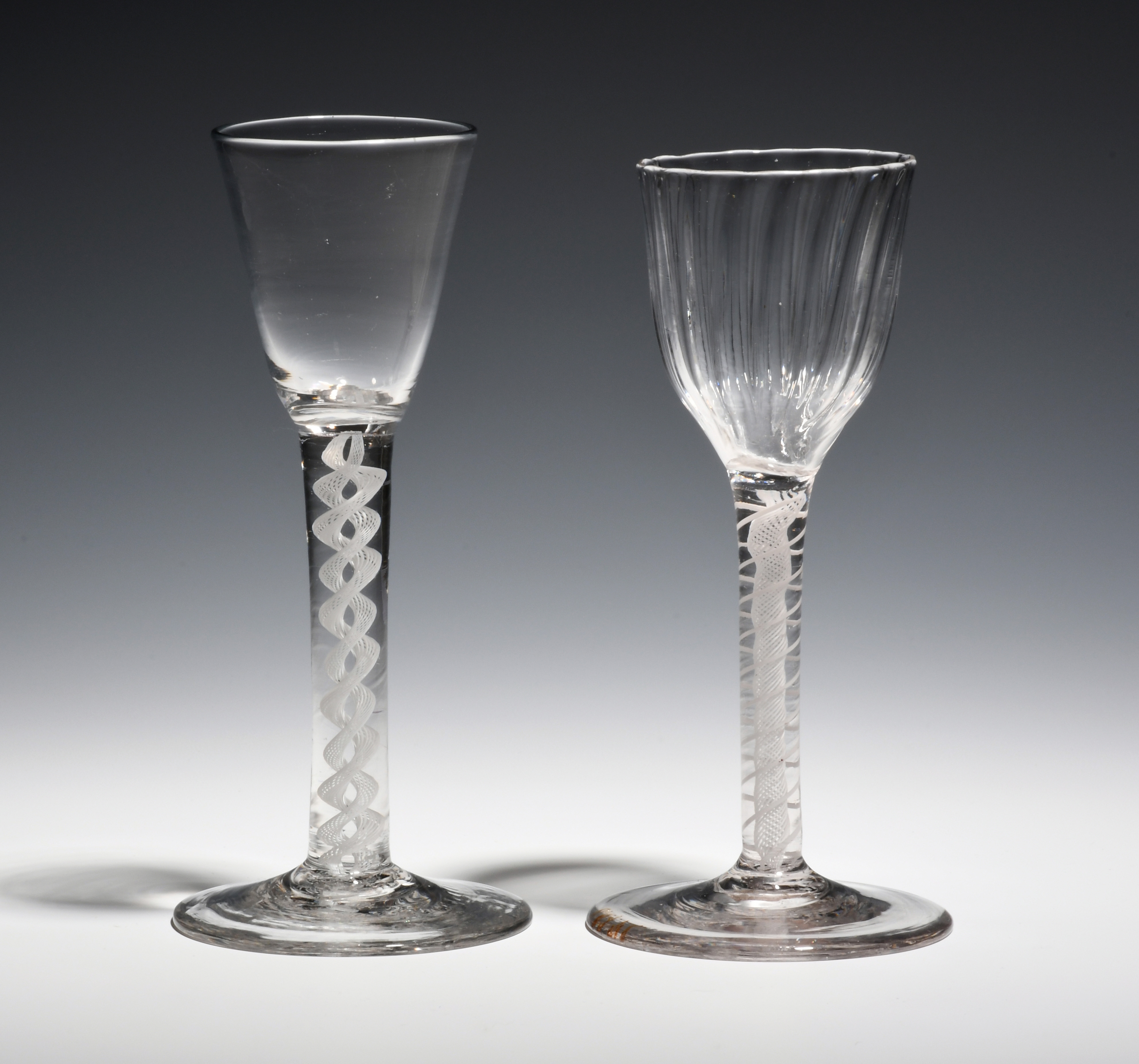 Two wine glasses c.1760-70, one with a round funnel bowl on an opaque twist stem, the other with a