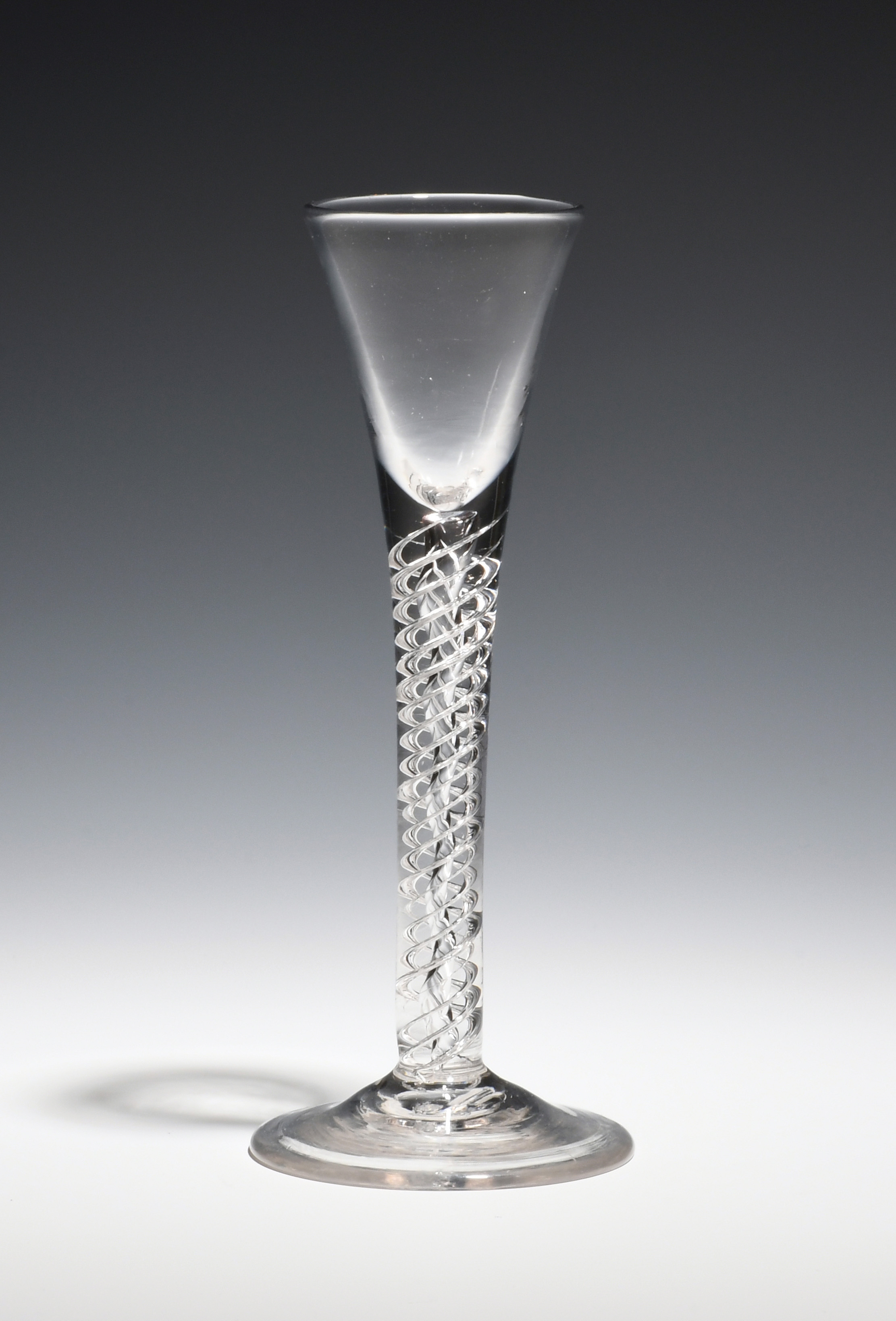A cordial glass c.1760, the drawn trumpet bowl raised on a double series mercury twist stem above