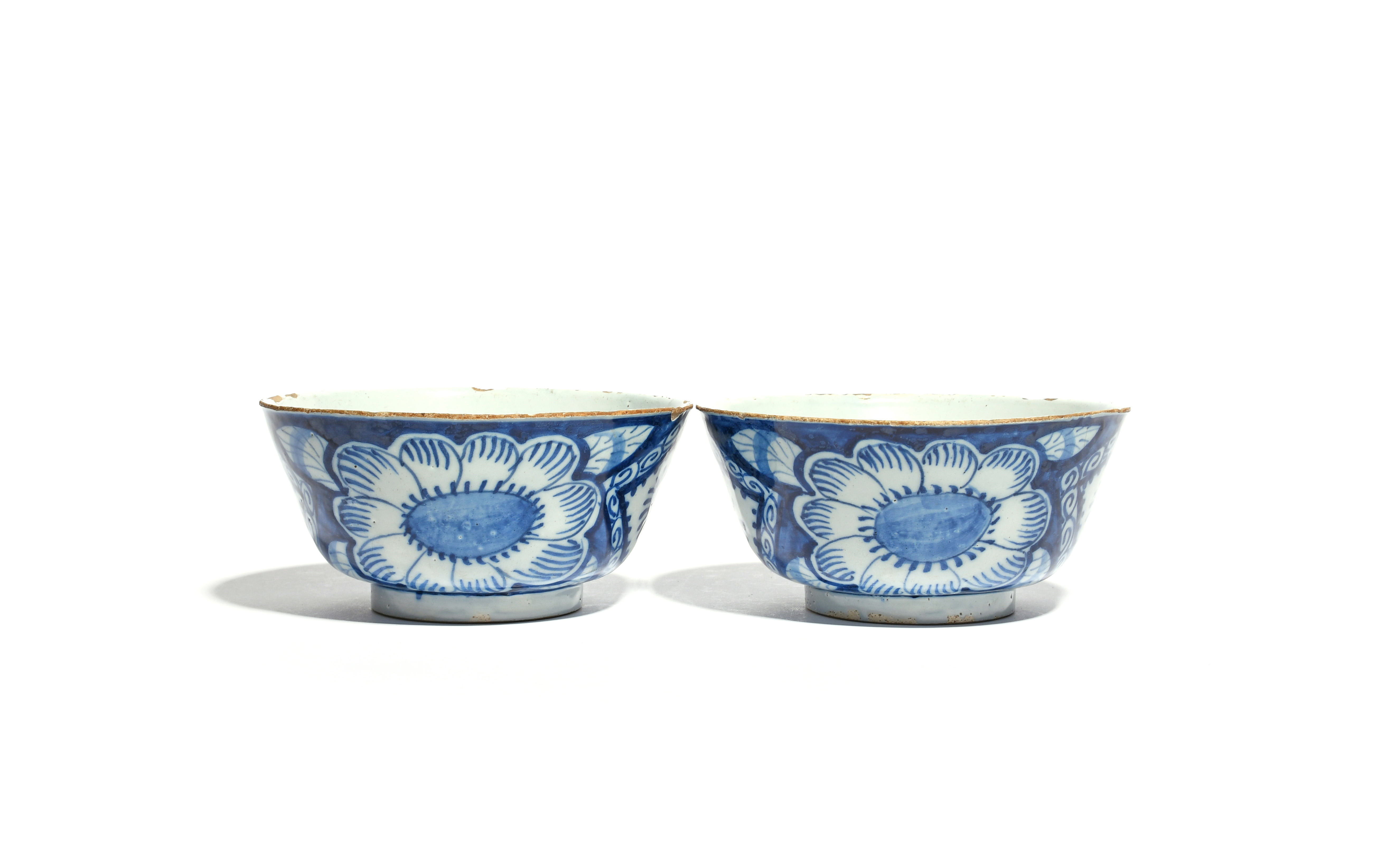 A pair of delftware bowls c.1730-40, the deep sides painted to the exterior with large flowerheads