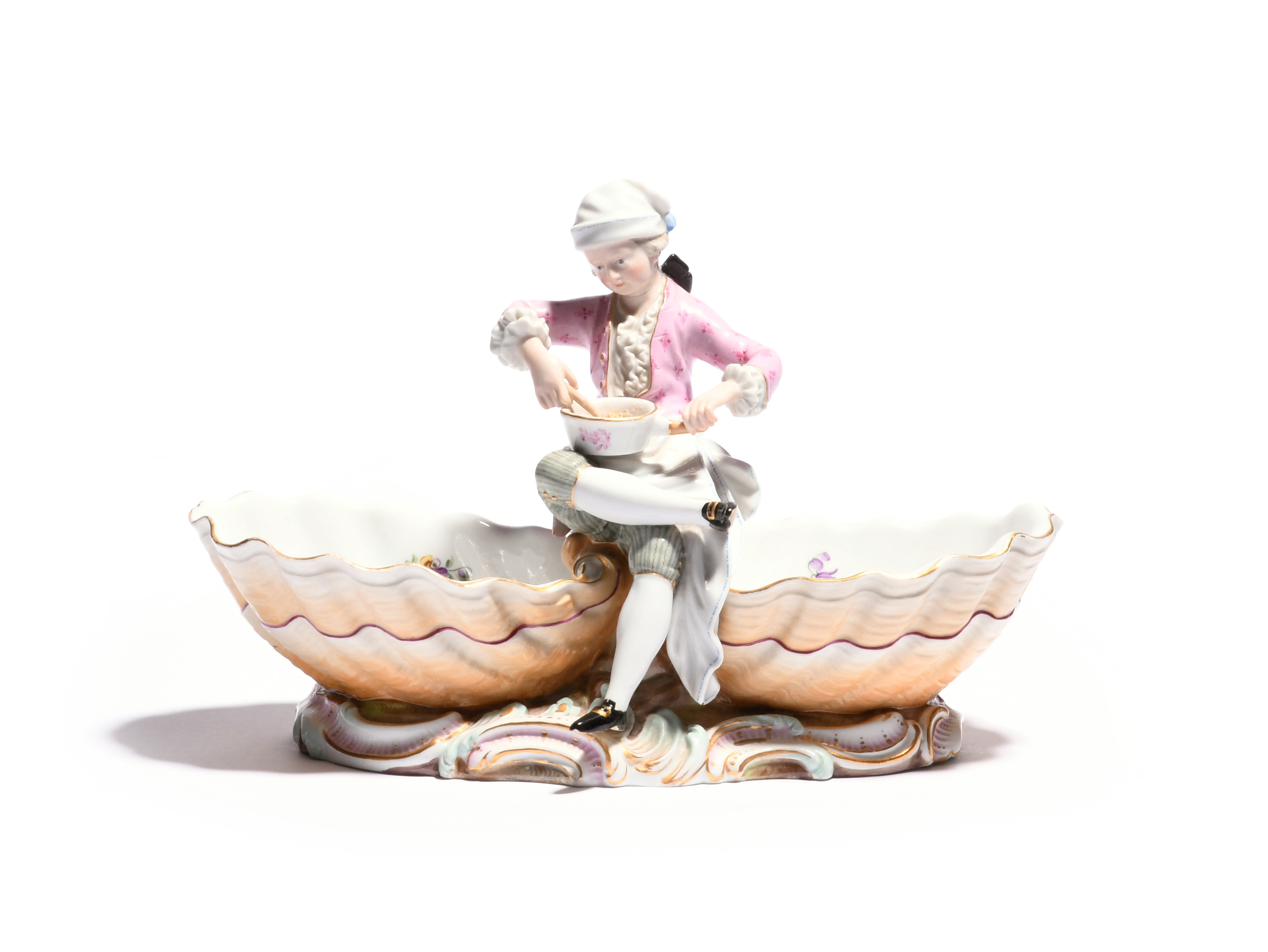 A Meissen sweetmeat figure 19th century, modelled as a young chef seated cross-legged between two