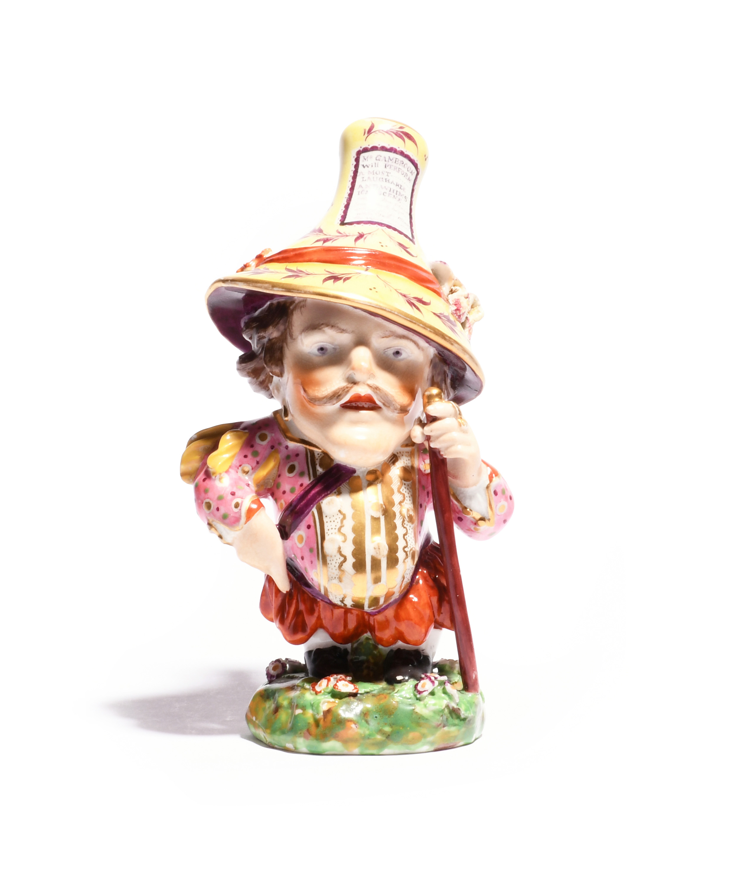 A Derby figure of a Mansion House Dwarf c.1810, wearing a comically large hat bearing a playbill for