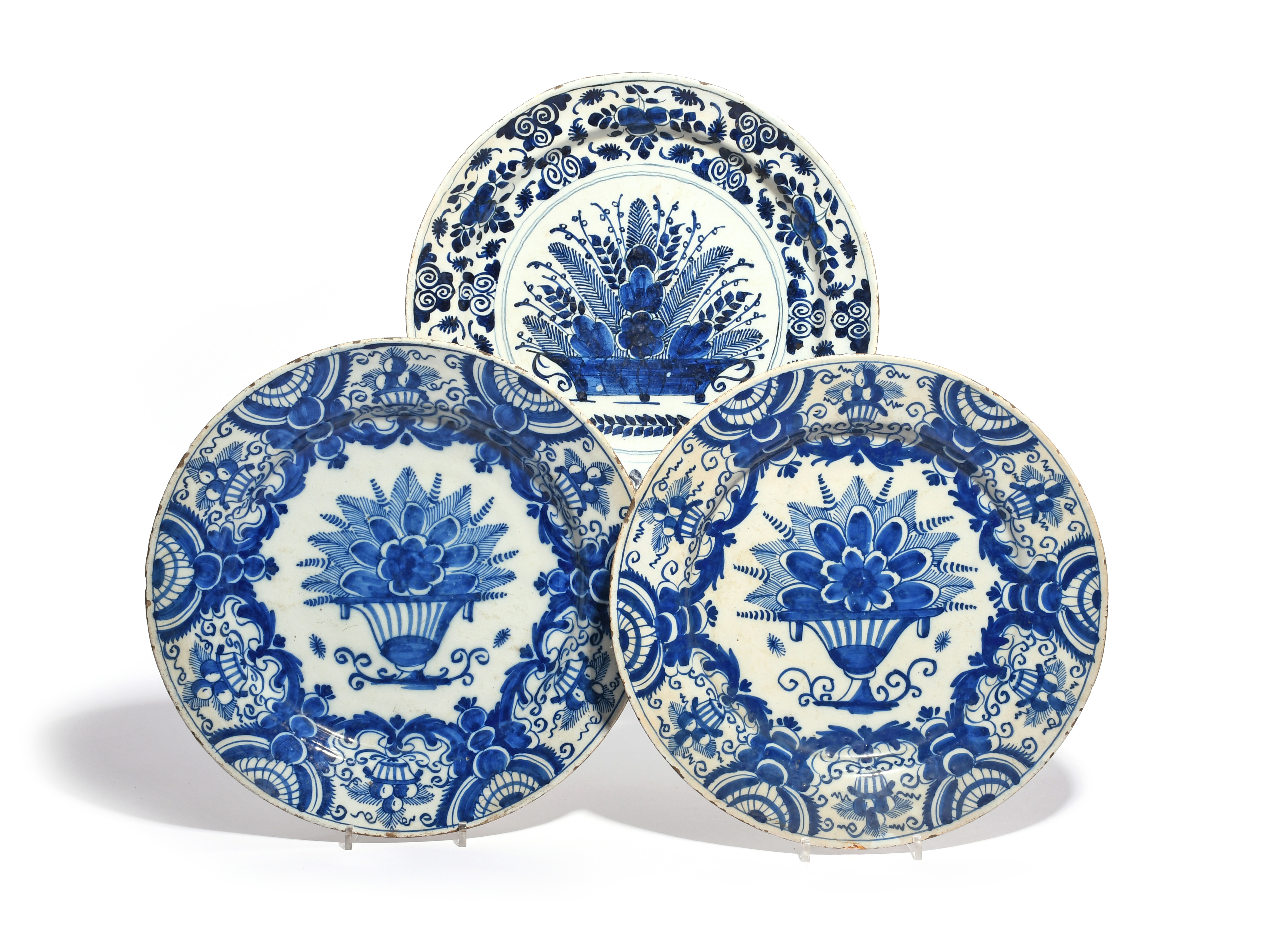 Three Delft chargers 18th century, variously painted in underglaze blue with vases and baskets of