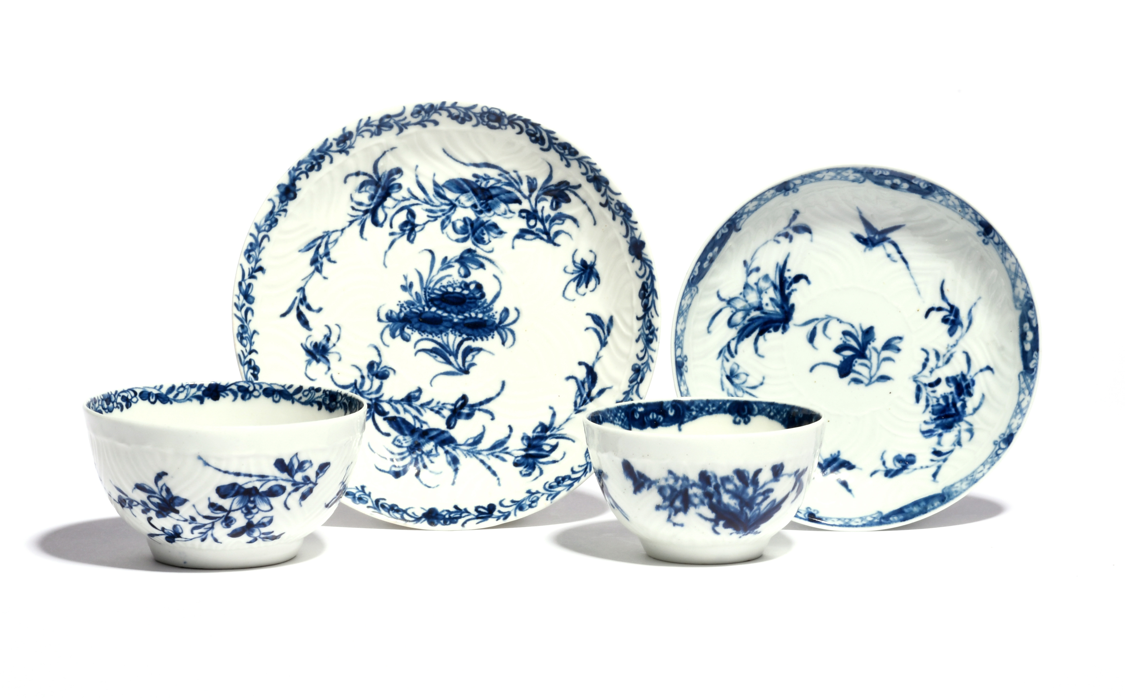Two Worcester blue and white teabowls and saucers c.1765, one painted with the Feather Mould Birds
