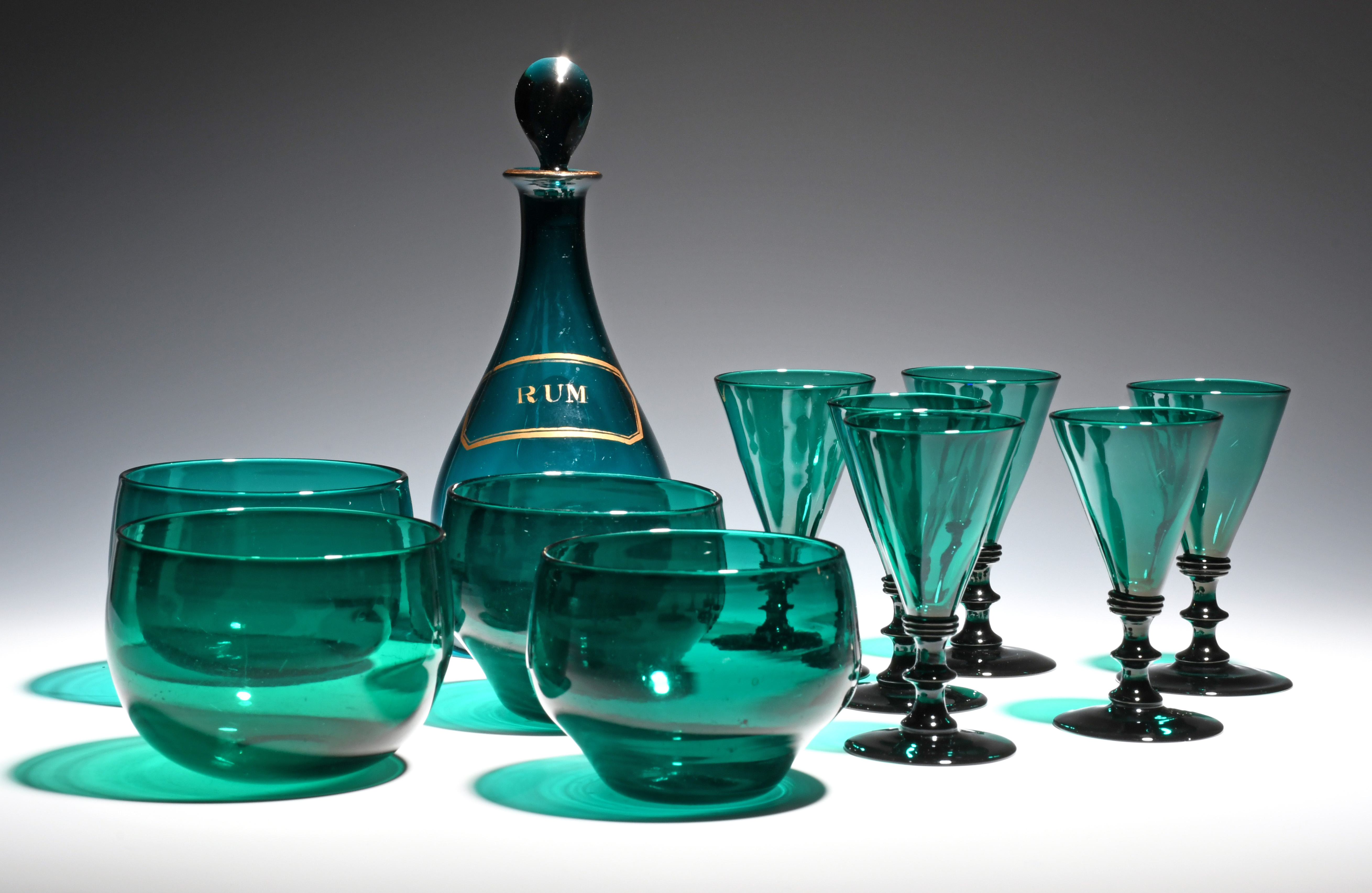 Six green wine glasses c.1800, with flared bowls raised on knopped and collared stems, a green glass