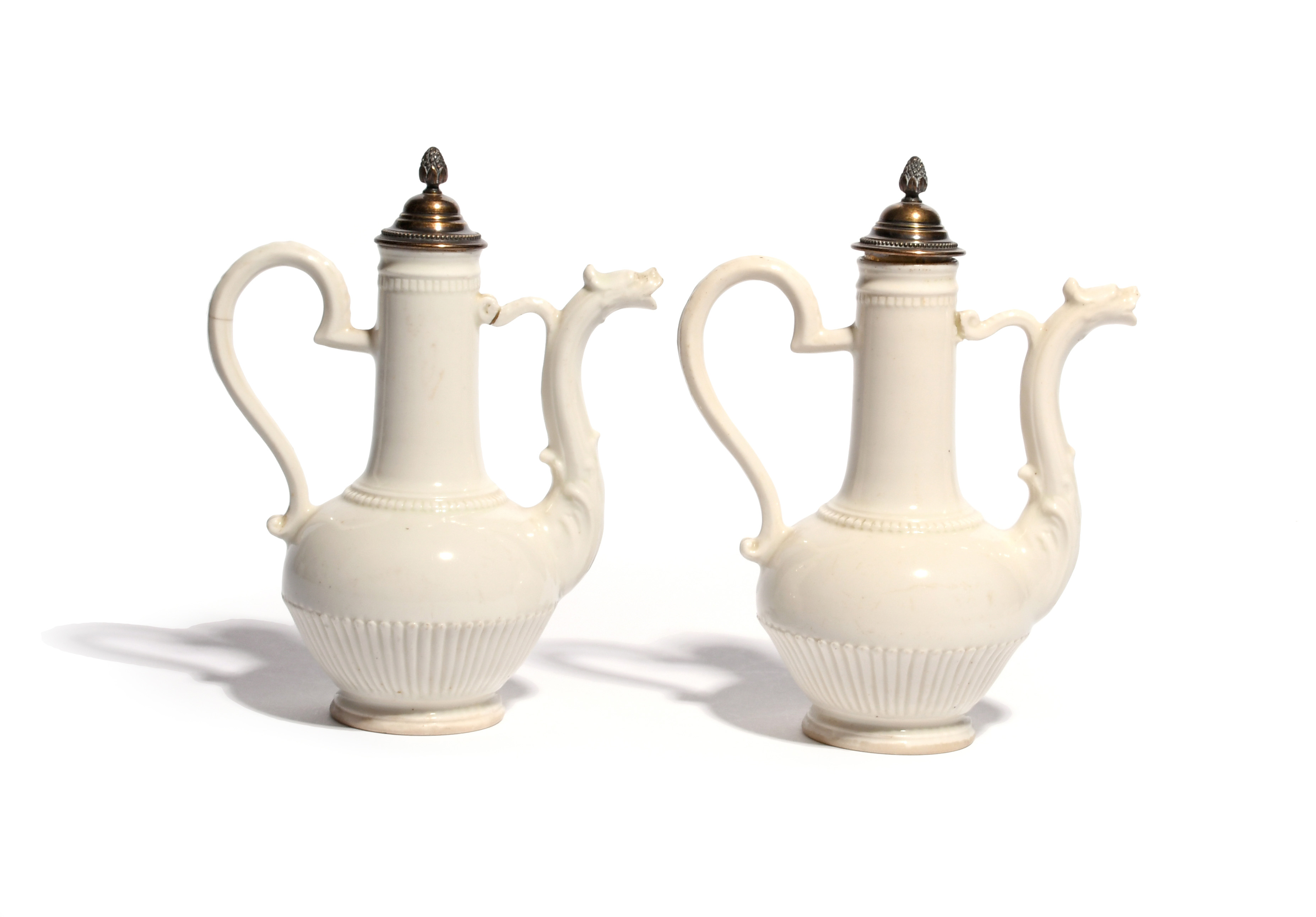 A pair of Italian porcelain ewers and silver covers c.1770, probably Buen Retiro, in the manner of