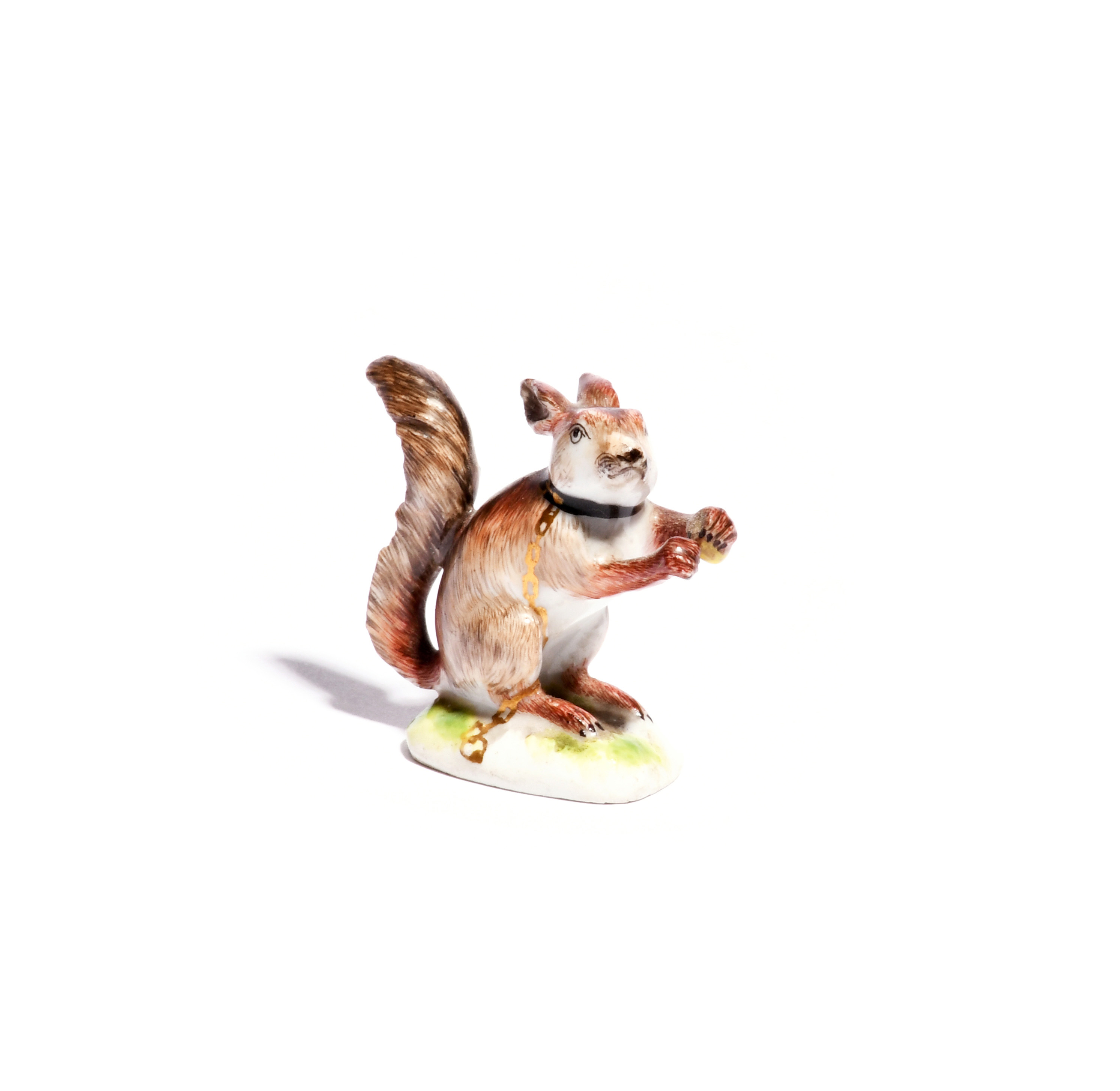 A miniature Meissen figure of a red squirrel c.1750, seated on its haunches in an alert position and