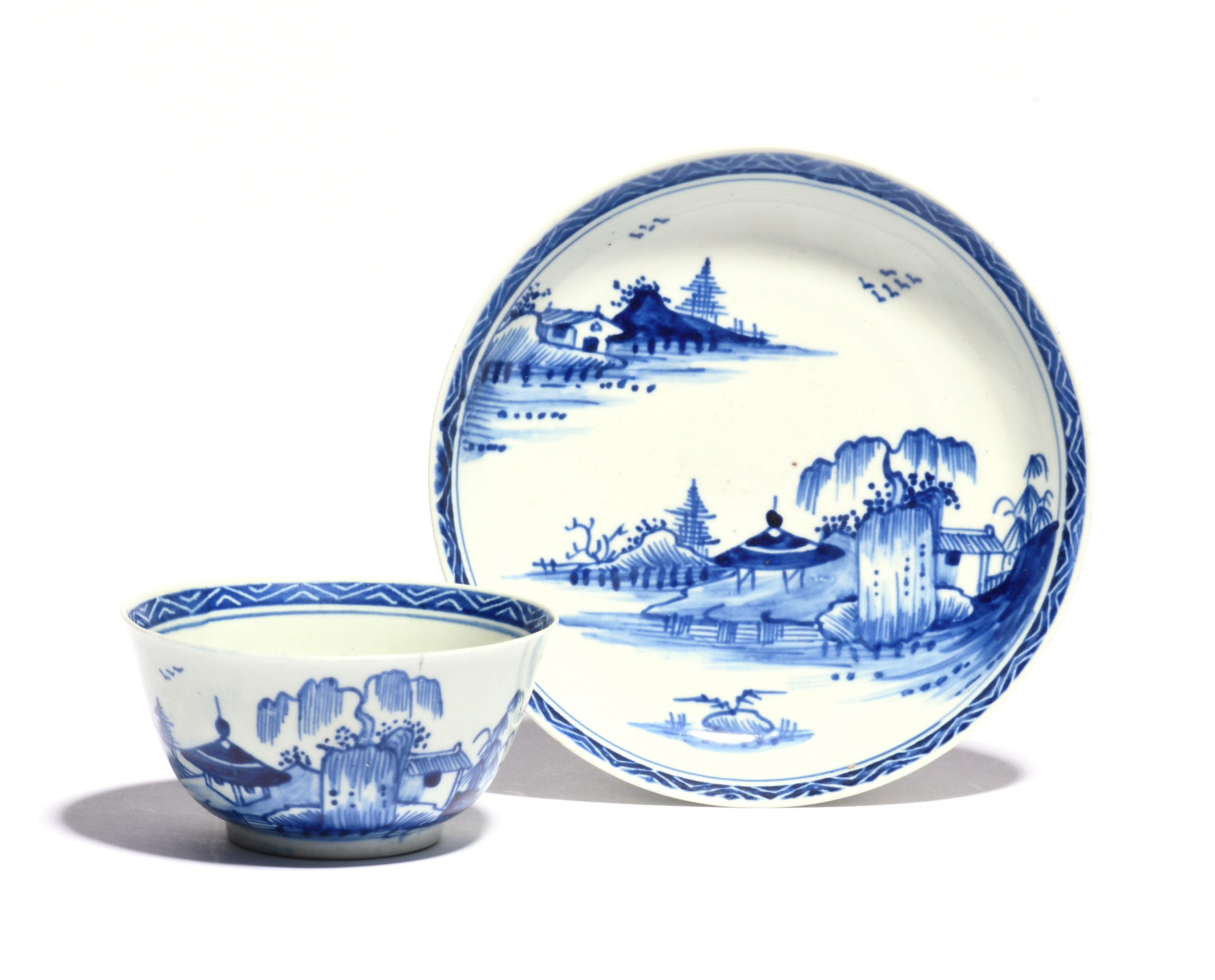 A Vauxhall blue and white teabowl and saucer c.1755-60, painted with low huts beneath willow in a