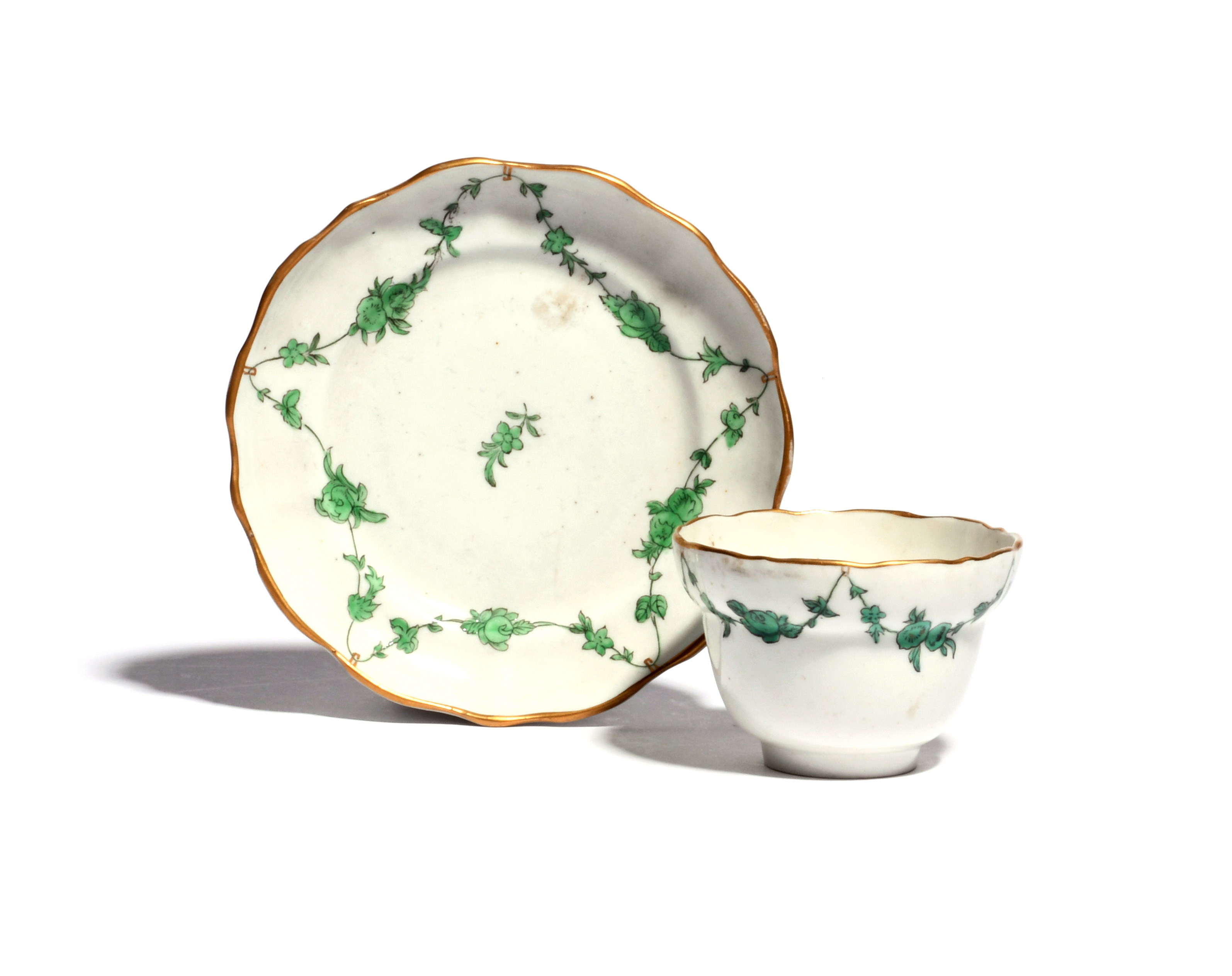 A small Bristol teabowl and saucer c.1775, of ogee shape, painted with loose flower garlands in