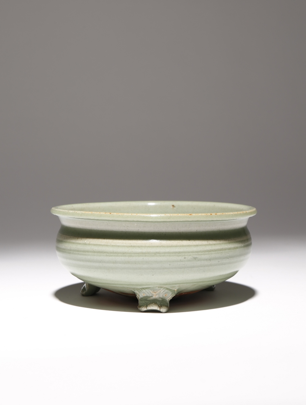 A CHINESE LONGQUAN CELADON TRIPOD INCENSE BURNER 15TH/16TH CENTURY The compressed body rising to