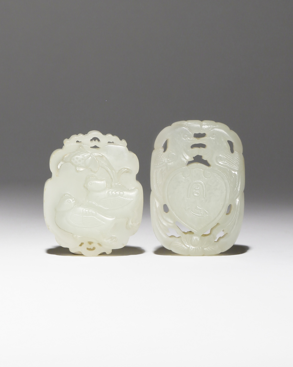 TWO CHINESE PALE CELADON JADE 'BIRDS' PENDANTS QING DYNASTY One carved in openwork with a pair of