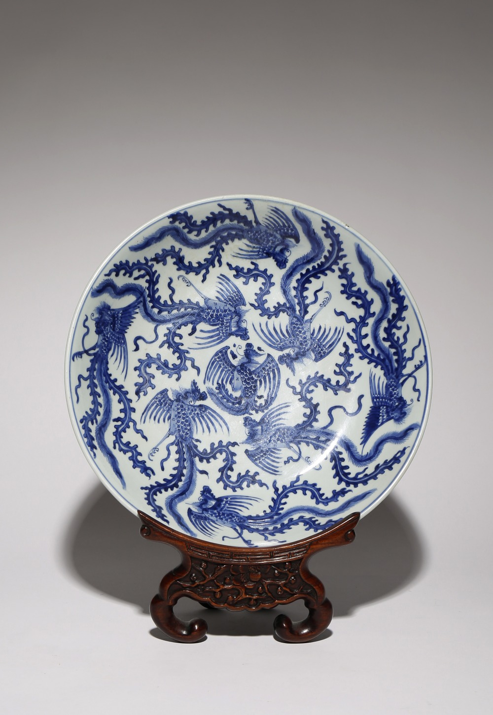 A LARGE CHINESE BLUE AND WHITE 'PHOENIX' DISH KANGXI 1662-1722 Rising from a tapering foot to an