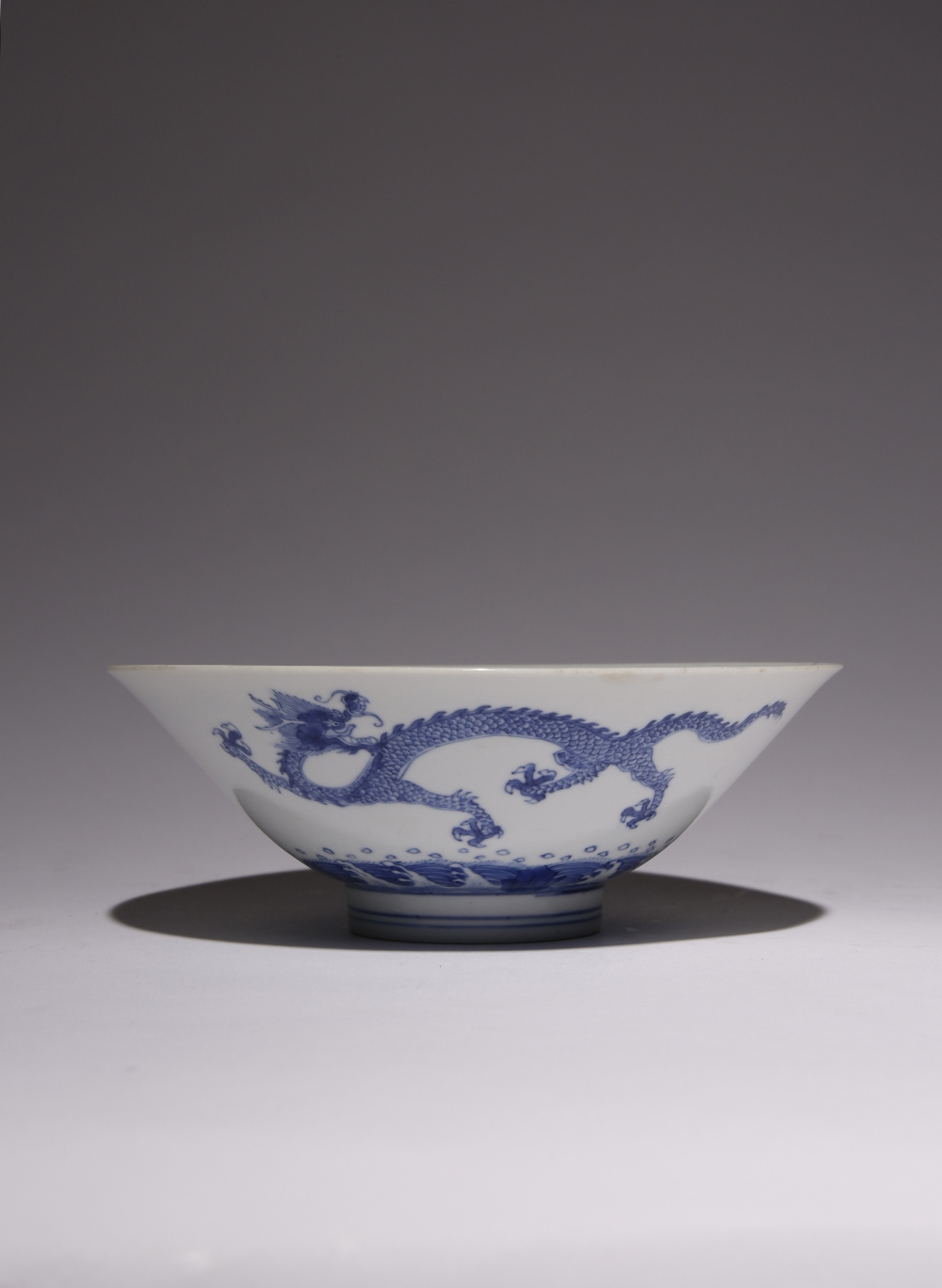 A CHINESE BLUE AND WHITE 'DRAGON' BOWL, DOULI WAN KANGXI 1662-1722 The flared body raised on a short