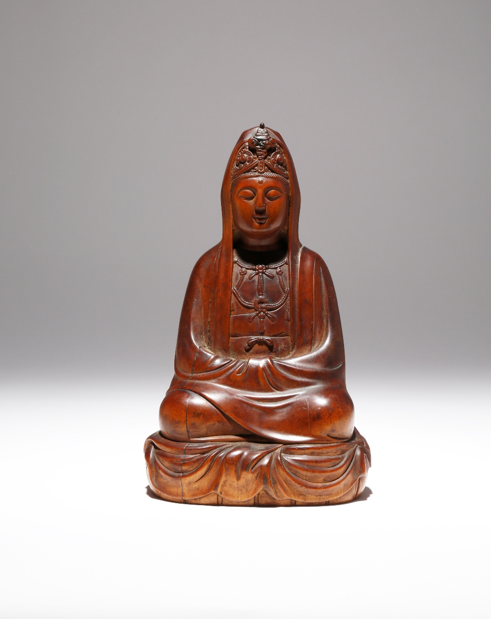 A CHINESE WOOD FIGURE OF GUANYIN QING DYNASTY The deity carved seated in dhyanasana with her hands