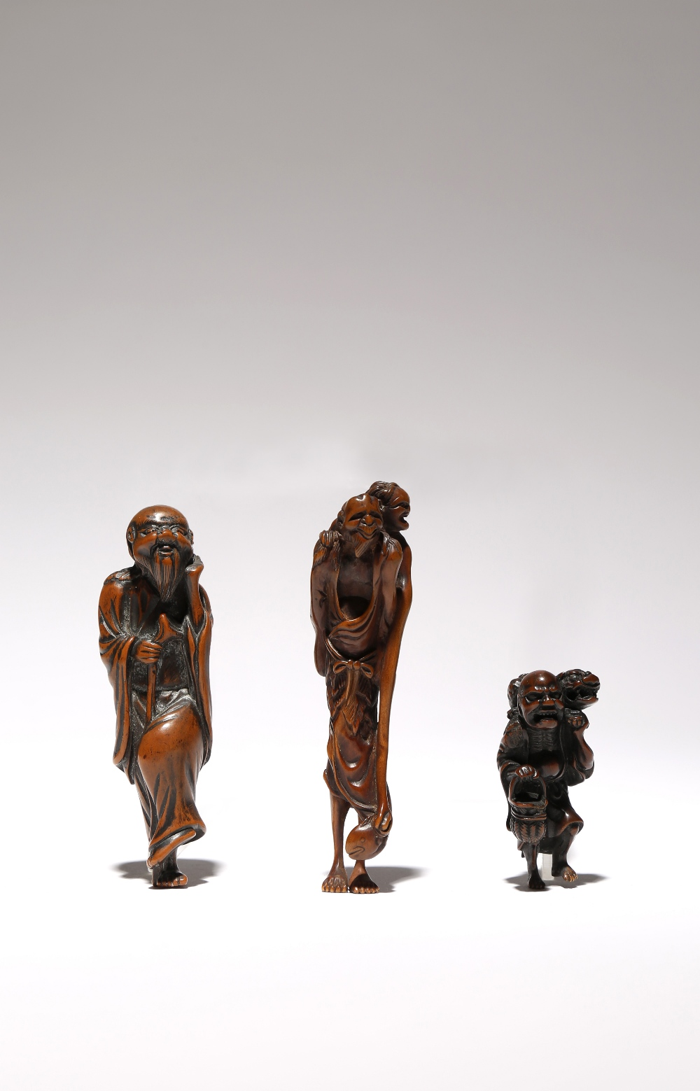 THREE JAPANESE WOOD NETSUKE OF FIGURES EDO AND MEIJI PERIODS, 18TH AND 19TH CENTURIES The tallest