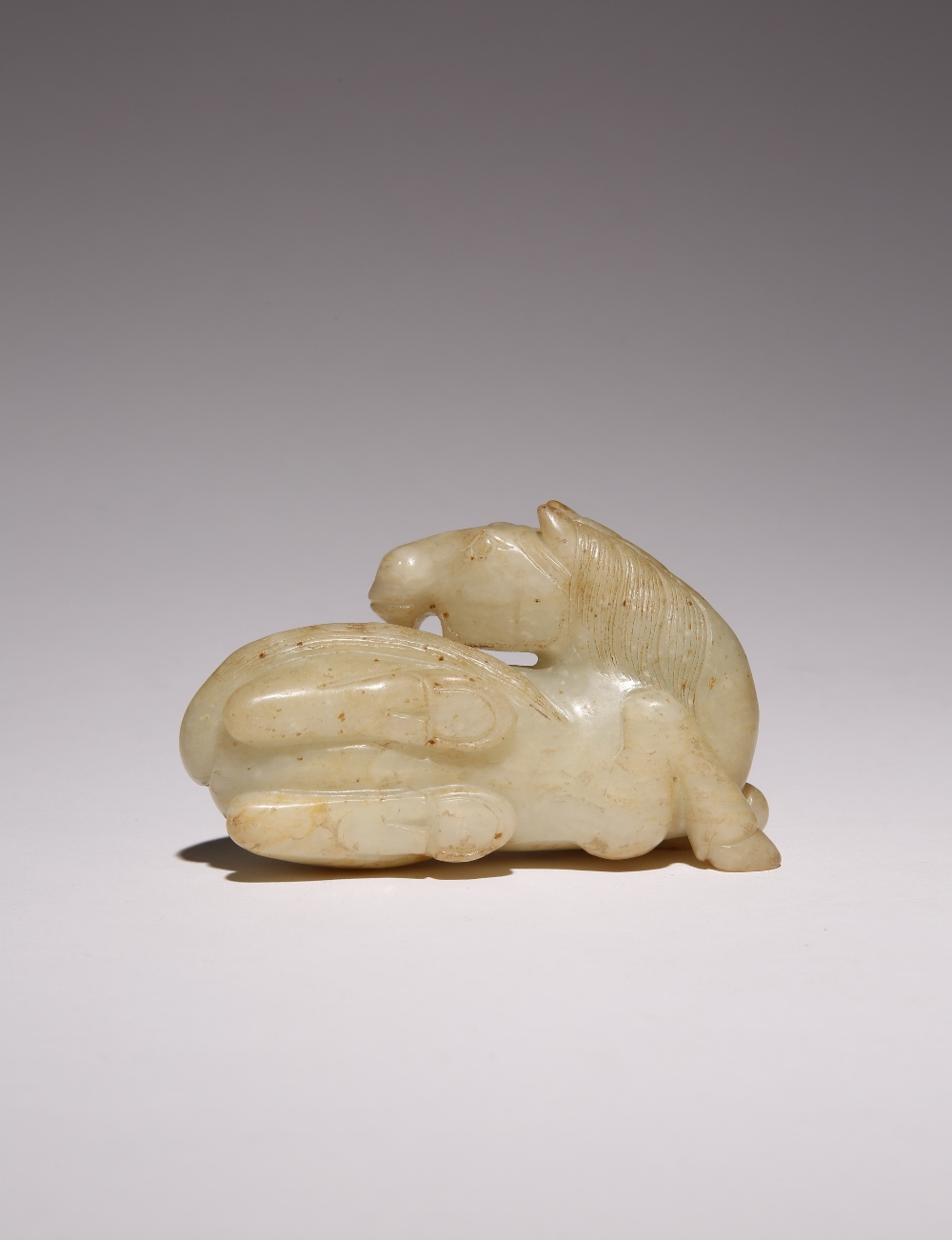 A CHINESE CELADON JADE CARVING OF A HORSE 17TH CENTURY OR LATER The recumbent horse turned looking - Image 2 of 2