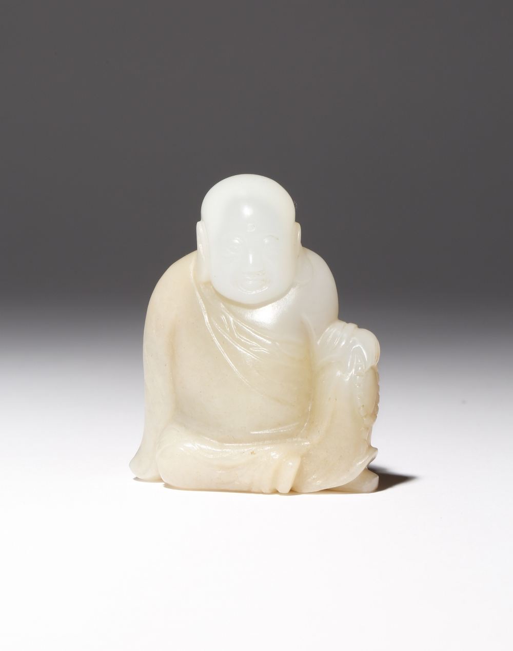 A CHINESE WHITE JADE CARVING OF A LUOHAN QING DYNASTY Depicted seated dressed in monk's robes, his