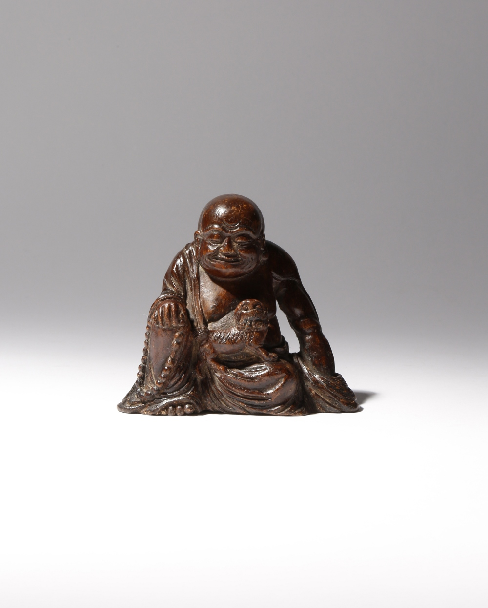 A CHINESE WOOD FIGURE OF A LUOHAN QING DYNASTY Probably aloeswood, the figure sits wearing loose
