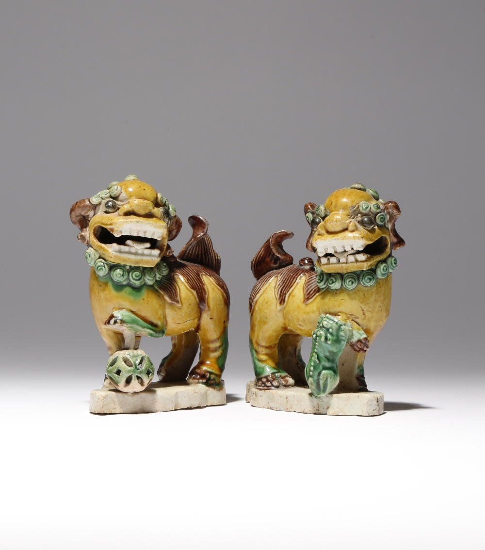A PAIR OF SMALL CHINESE SANCAI MODELS OF LION DOGS KANGXI 1662-1722 The beasts depicted with bulging