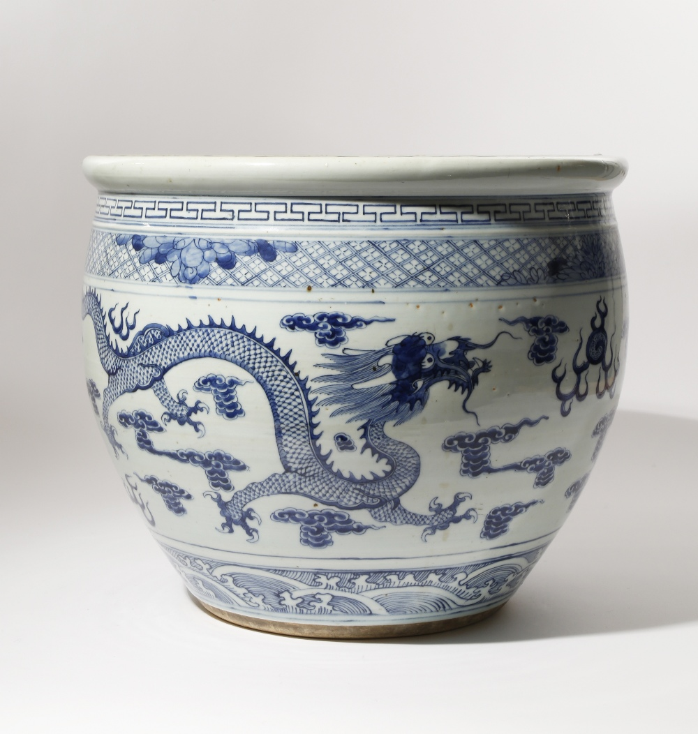 A LARGE CHINESE BLUE AND WHITE 'DRAGONS' JARDINIERE 19TH CENTURY The deep ovoid body painted with