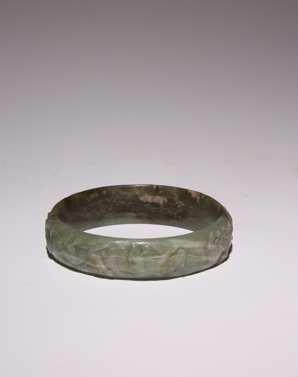 A CHINESE CELADON JADE 'EIGHT HORSES' BANGLE QING DYNASTY OR LATER Carved to the exterior with the
