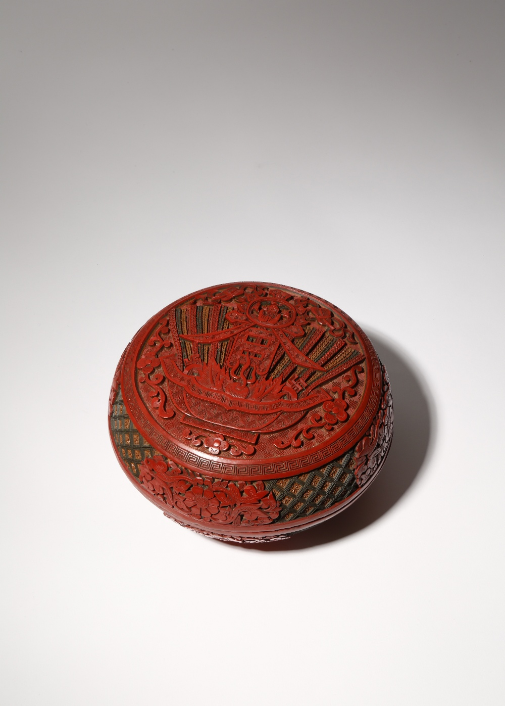 A CHINESE THREE-COLOUR CINNABAR LACQUER CIRCULAR BOX AND COVER 19TH CENTURY Carved with a bowl