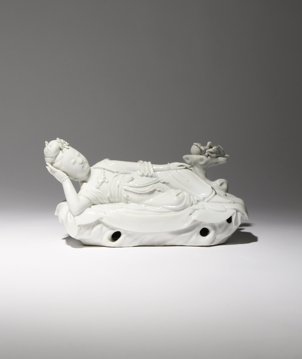 A CHINESE BLANC DE CHINE FIGURE OF GUANYIN 18TH CENTURY Depicted reclining on a large plantain